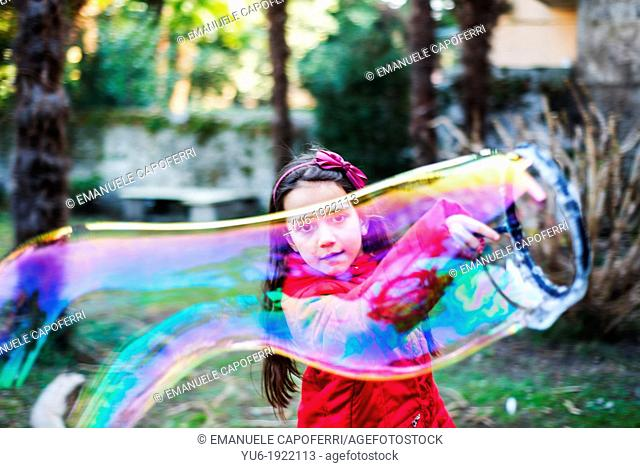 Child makes giant soap bubbles in a garden of Lake Maggiore, Ispra, Varese, Italy