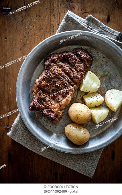 Grilled ribeye steak with potatoes