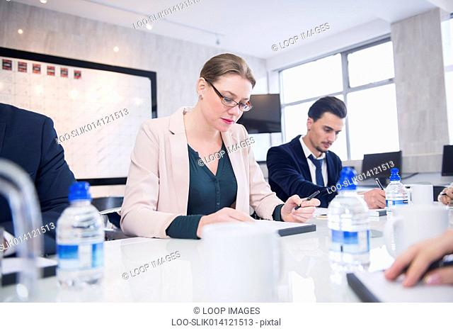 Professional people sitting in an office environment having a discussion during a production meeting