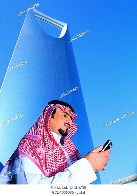 Saudi Businessman outside Al Mamlakah Kingdom Tower in Riyadh, Saudi Arabia