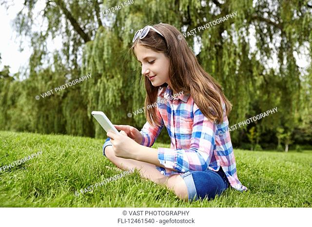 Preteen girl sitting in a park holding a tablet; Toronto, Ontario, Canada