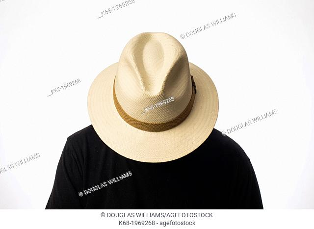 a man wearing a straw fedora hat over his face