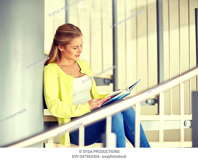 smiling high school student girl reading book