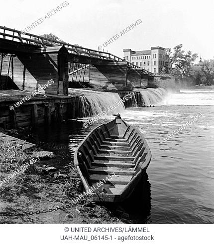 Ein Boot liegt unter einer Brücke am Ufer der Mulde in Dessau, Deutschland 1930er Jahre. A boat at the shore of river Mulde at Dessau, Germany 1930s