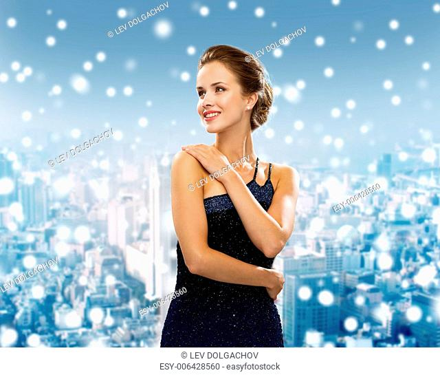 holidays, christmas and people concept - smiling woman in evening dress over snowy city background
