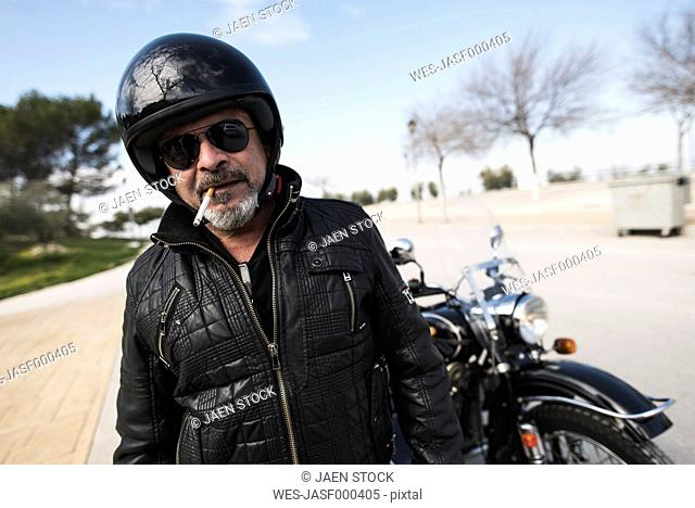 Portrait of smoking biker wearing helmet and sunglasses standing on a road in front of his motorcycle