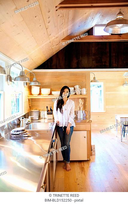 Chinese woman standing in rustic kitchen