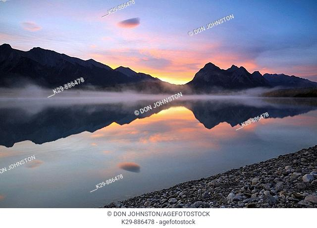 Sunrise skies and morning fog over Abraham Lake in autumn