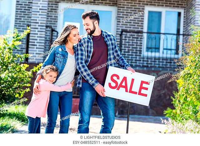 young beautiful family standing in front of house on sale
