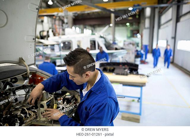 Mechanic repairing helicopter engine in airplane hangar