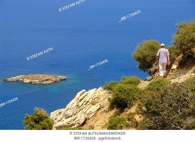Woman hiking along a steep coastal cliff trail, looking over an island and the blue sea, descending from Moutti tis Sotiras mountain, Baths of Aphrodite, Akamas
