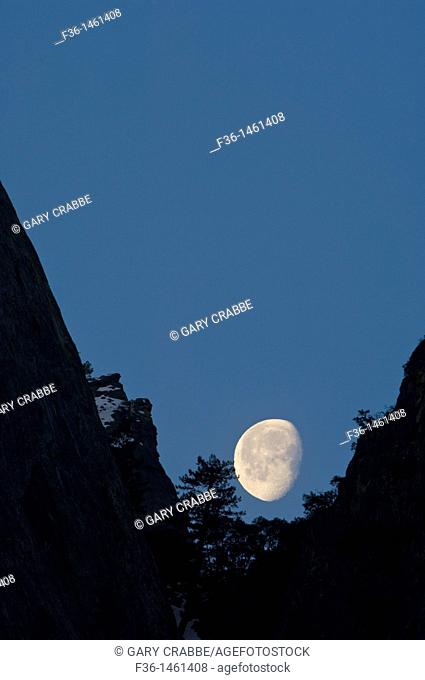 Waning gibbous moon setting behind mountain cliff, Yosemite National Park, California