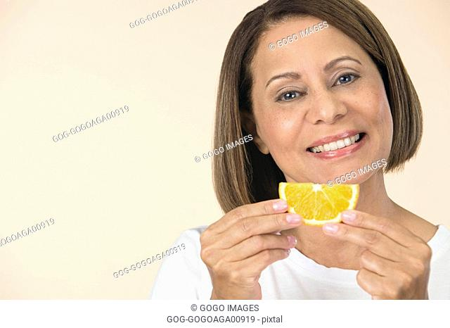 woman holding orange slice