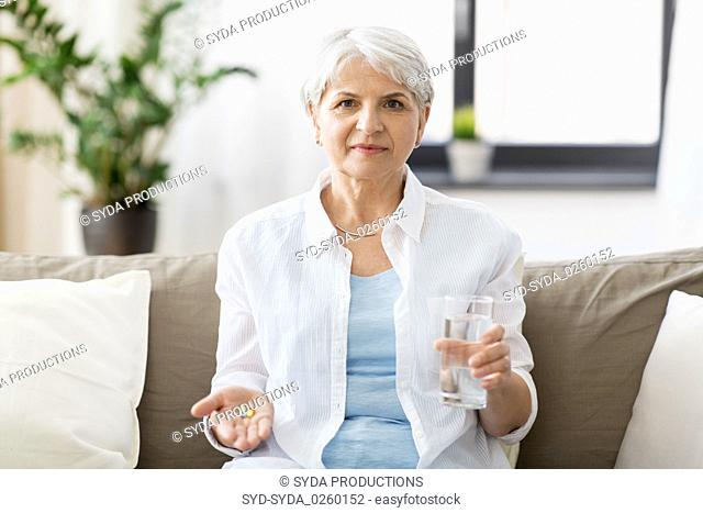 senior woman with water and medicine at home