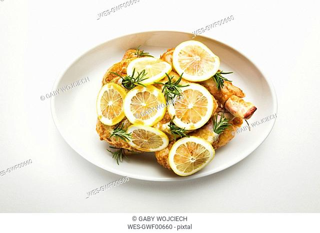 Row chicken and lemon slices on plate