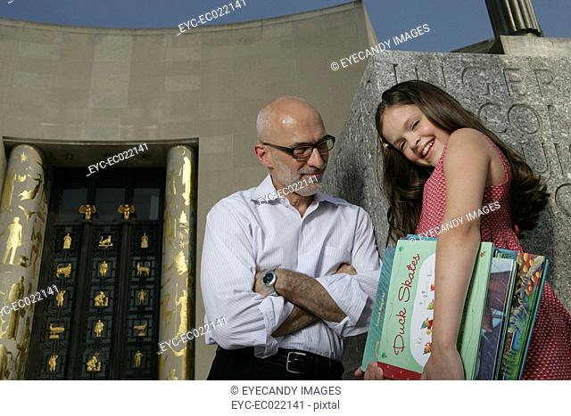 mature man talking to girl with school books