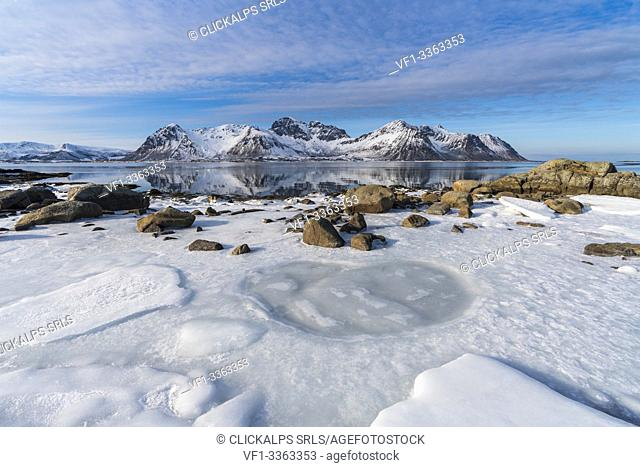 Ice on the beach with Limstrandtinden snowcapped group in the background. Vestvagoy municipality, Lofoten district, Nordland county, Norway