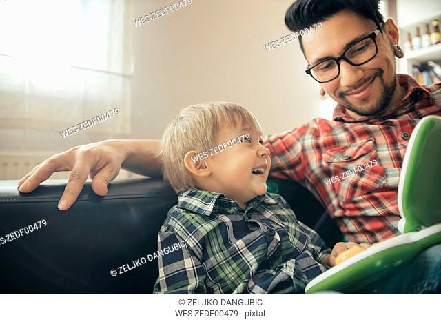 Happy father and son with toy laptop