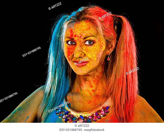 Young woman covered with paints over black background