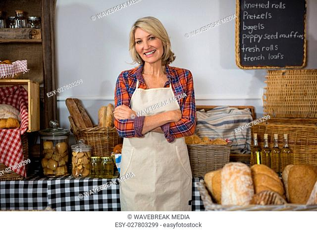 Portrait of smiling female staff standing with arms crossed at counter