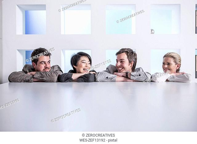 Four smiling colleagues in office
