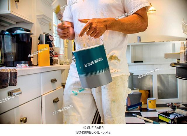 Cropped view of man in kitchen holding paint can