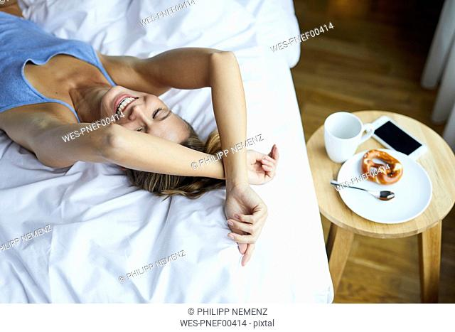 Laughing young woman lying in bed