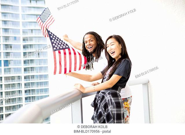 Couple waving American flags on urban balcony