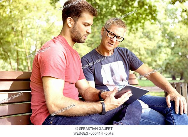 Two men sitting on a park bench looking at digital tablet