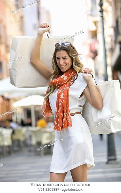 Pretty blonde woman happy shopping in downtown