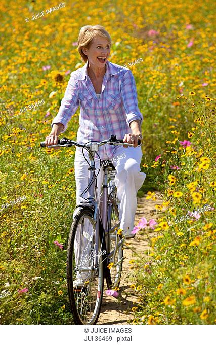 Enthusiastic woman riding bicycle among wildflowers in sunny meadow