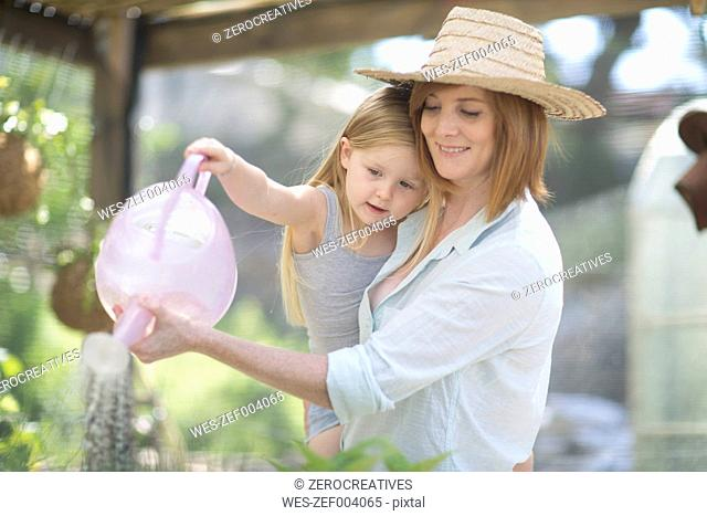 Portrait of woman and little daughter watering plants with watering can