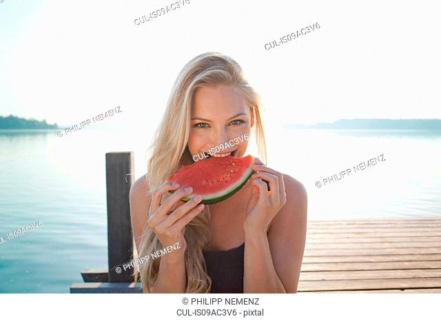 Portrait of young woman at lake eating watermelon
