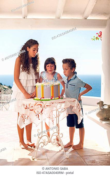 Children blowing out birthday candles