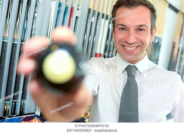 young handsome businessman holding billiard ball