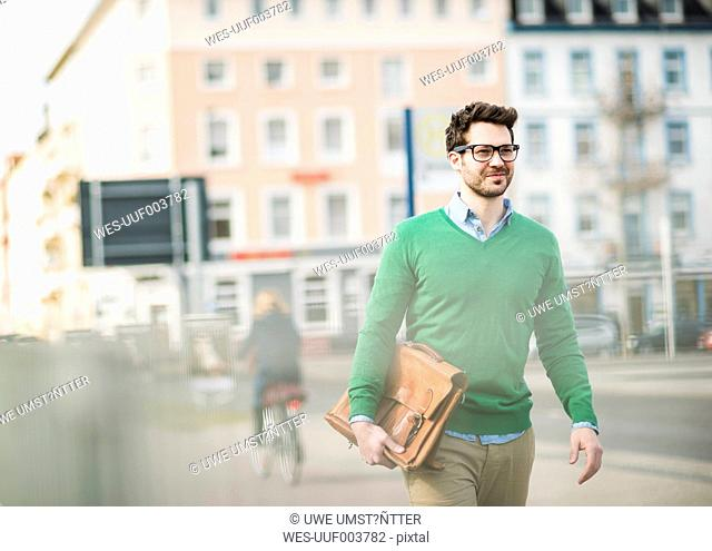 Man in green sweater carrying briefcase