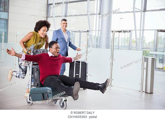 Playful couple running with luggage cart in airport
