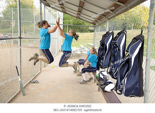 Soft ball players jumping and giving a high five