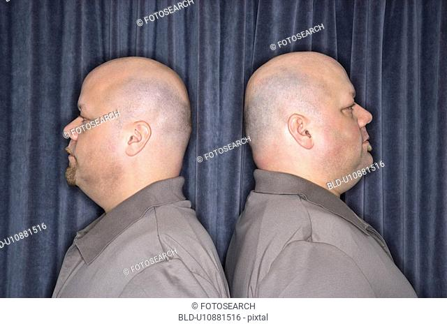 Profile of bald identical twin mid adult men standing back to back