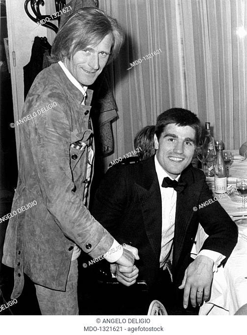 Nino Ferrer and Nino Benvenuti during a party. Italian-born French singer and jazz player Nino Ferrer (Agostino Arturo Maria Ferrari) shaking hands with Italian...