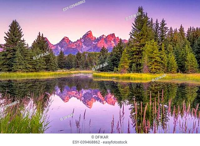 The Teton range's reflection upon the Snake River. Photographed at dawn at Schwabacher's Landing in Grand Teton National Park, WY