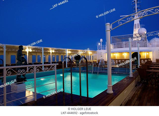 Swimming pool and cruise ship MS Deutschland (Reederei Peter Deilmann) at dusk, Atlantic Ocean, near Greenland
