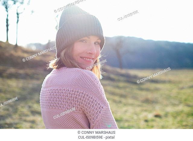 Sunlit portrait of mid adult woman in sunlit field looking over her shoulder