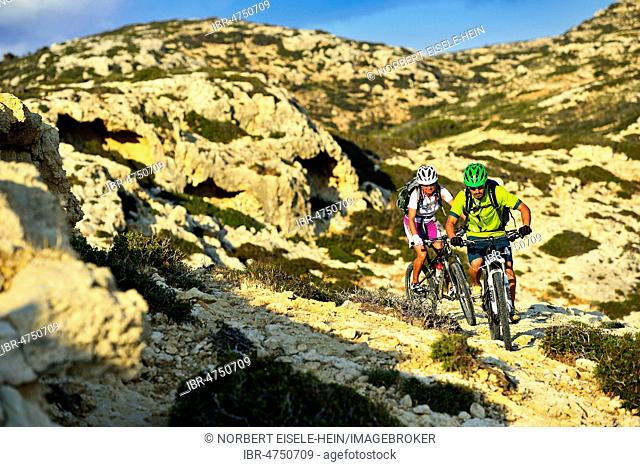 Two mountain bikers cycle in rocky terrain, Red Beach, Matala, Crete, Greece