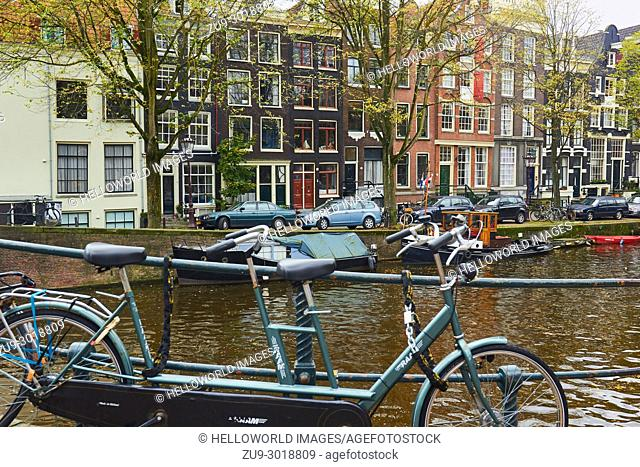 Tandem bicycle chained above canal, Amsterdam, Netherlands