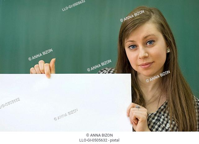 Young woman, classroom holding white blank billboard, Debica, Poland