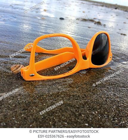 Dumped broken sunglasses near the sea on the beach