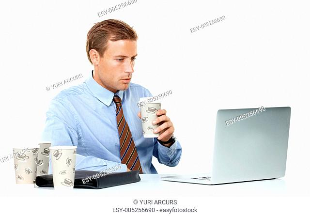 A drowsy young businessman drinking coffee for a boost while working late