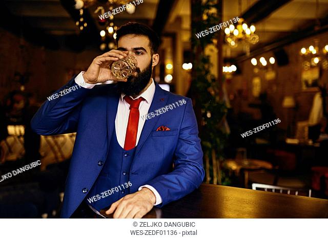 Eegant young man in a bar drinking from tumbler