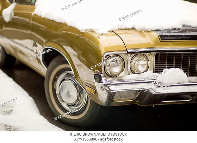 A classic Oldsmobile is partially covered in snow